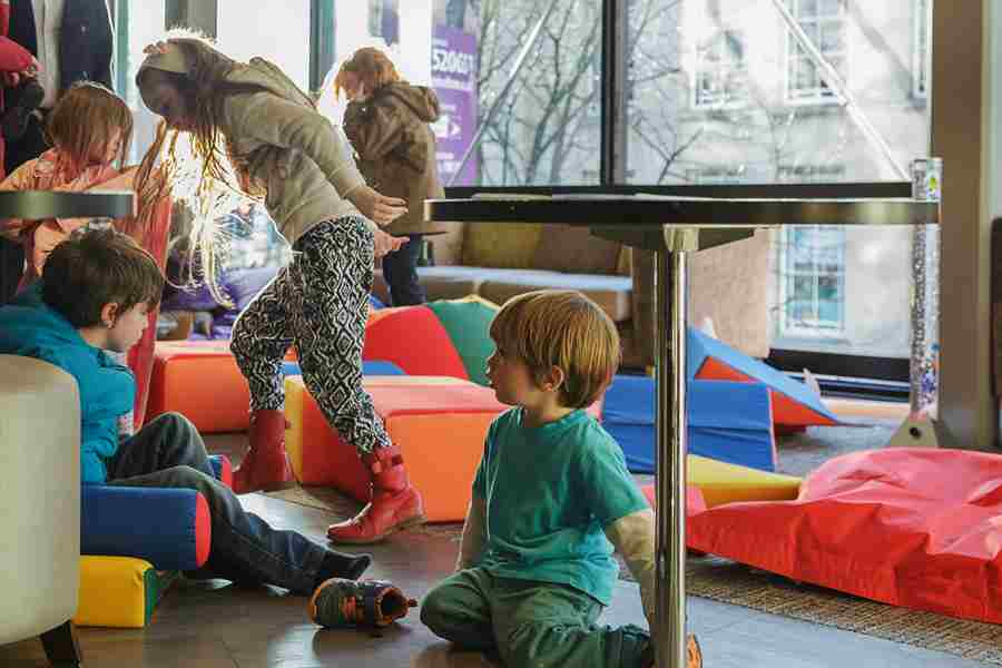 Children play in the soft breakout area during a relaxed performance